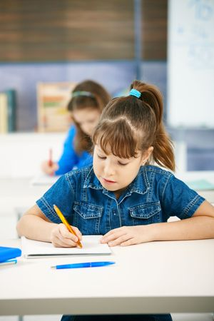 Young girl writing at school sitting in class with other girl in background. photo