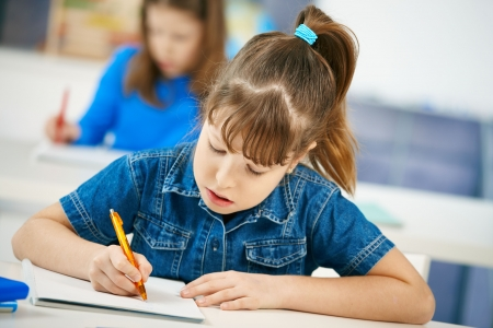 american children: Young girl writing at school sitting in class with other girl in background.