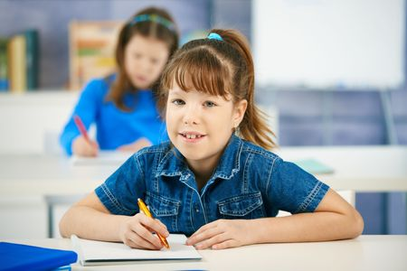 elementary students: Portrait of elementary age schoolgirl sitting in class looking at camera smiling, other girl in background.
