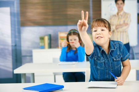 Schoolgirl raising hand to answer question smiling, other girl and teacher in background of class. photo