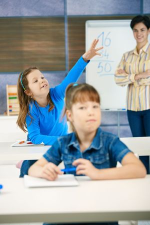 raised hand: Schoolgirl in focus sitting in back row of class with raised hand, smiling, teacher standing at blackboard.