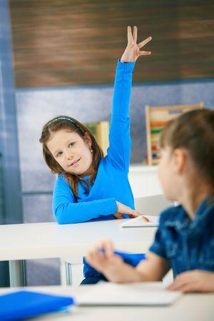 Portrait of smiling elementary age schoolgirl raising hand in class. Stock Photo - 6463827