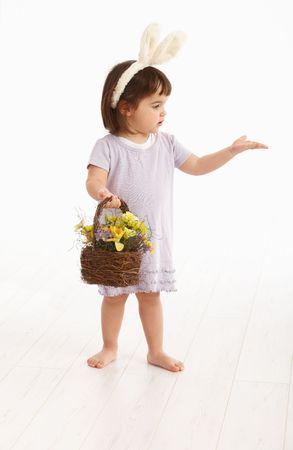 3 persons only: Little two years old girl wearing Easter bunny ears, isolated on white background.