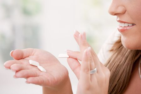 Partially visible young woman holding chewing gums in her hand. Stock Photo - 6473203