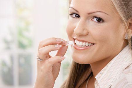 -Guma do żucia: PiÄ™kne mÅ'oda kobieta jedzenia chewing gumy, uÅ›miechniÄ™ta.  Zdjęcie Seryjne