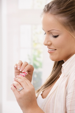 Beautiful girl taking pink chewing gum, smiling. Side view portrait. Stock Photo - 6473209