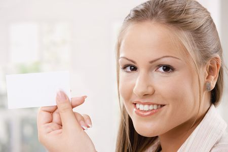 Beautiful young woman holding an blank card with copy space.   photo