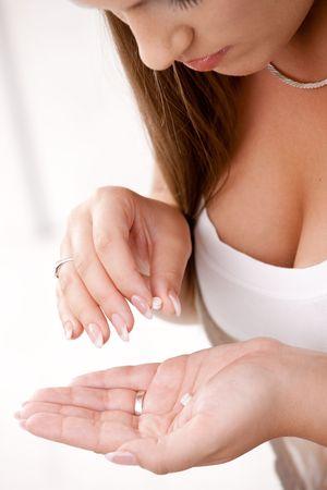 Closeup of young woman girl taking pills. Stock Photo - 6473189