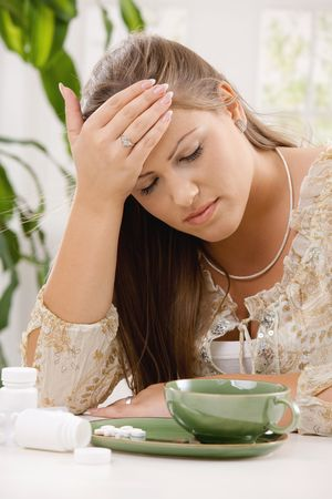 Young woman having headache, holding her head, leaning on table. Taking pills with tea. photo