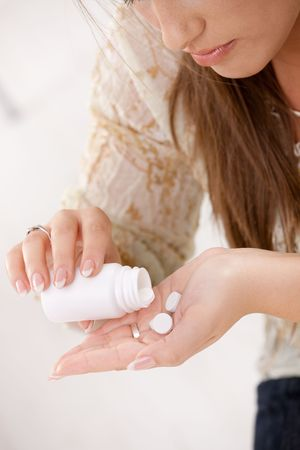 painkiller: Closeup of young woman girl taking pills from bottle.