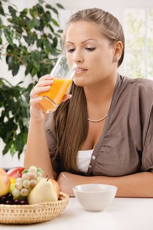 Young woman sitting at table having breakfast, drinking orange juice. photo