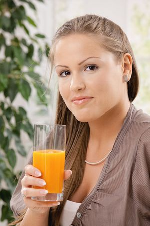 Closeup portrait of beautiful young woman drinking orange juice. Stock Photo - 6473270