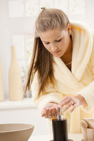 Young woman wearing bathrobe washing hands at home in bathroom. photo