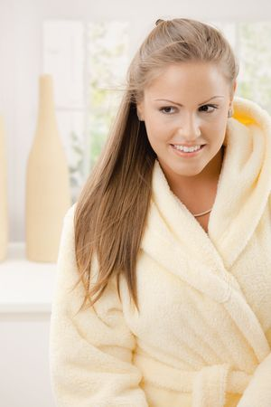 Portrait of happy young woman wearing yellow bathrobe, smiling. photo