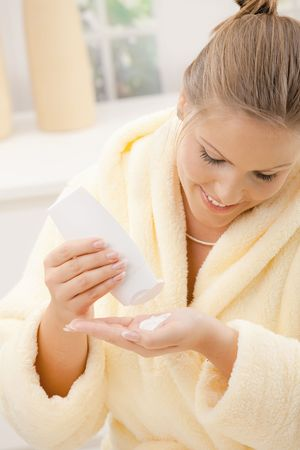 Young woman wearing bathrobe, using body lotion, smiling. photo