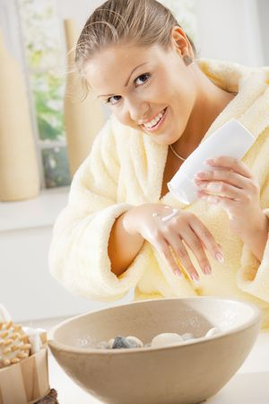 Happy young woman wearing bathrobe, using hand cream, smiling. photo