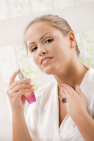 Young woman wearing white silk bathrobe applying perfume, smiling. photo