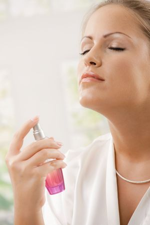 Closeup portrait of young woman wearing white silk bathrobe applying perfume, eyes closed. photo