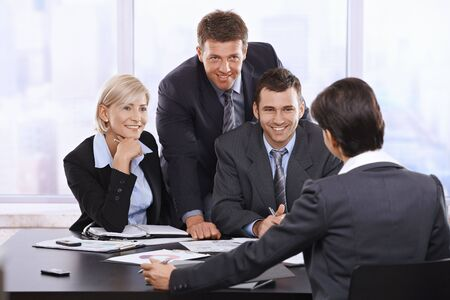 Smiling businesspeople at meeting looking at executive in office. photo