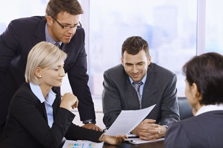 woman with document: Businesspeople reviewing contract at meeting in office.