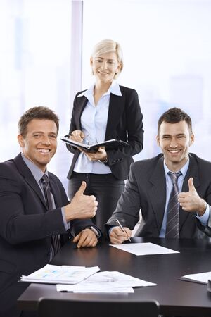 Successful team portrait with smiling businessmen giving thumbs up looking at camera, businesswoman holding organizer smiling. photo