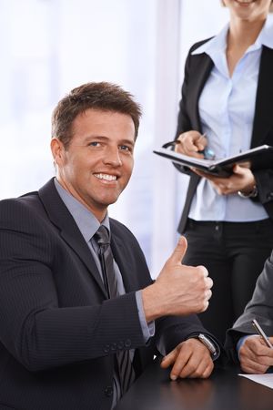 Successful businessman giving the thumb up, smiling at meeting happily. photo
