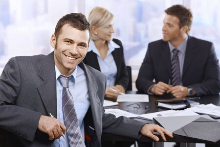 Smiling businessman looking at camera sitting at meeting table, coworkers in background. photo
