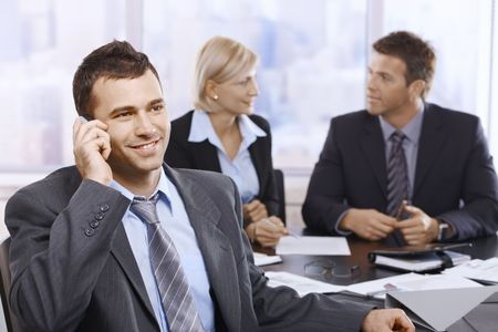 human cell: Businessman on phonecall in office meeting with colleagues sitting in background.