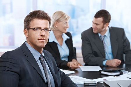 co work: Portrait of businessman looking at camera sitting at meeting room with partners. Stock Photo