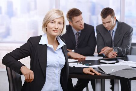 Confident businesswoman sitting at meeting in office with colleagues working in background. photo