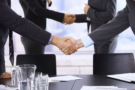 situation: Businesspeople shaking hands in skyscraper office after meeting. Stock Photo