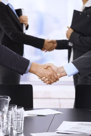 Businesspeople shaking hands in skyscraper office on meeting. photo