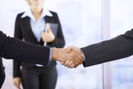 Businessmen shaking hands in office, assistant in background, handshake in closeup. photo