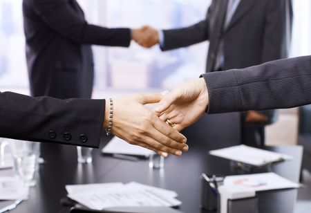 Businesspeople shaking hands in skyscraper office on meeting. Focus on hands. Stock Photo - 6508270