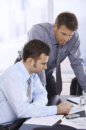 Mid-adult businessmen working together in office. photo