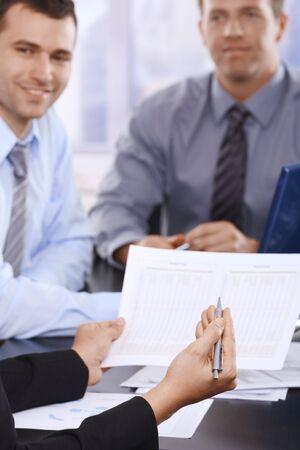 Business documents handheld in focus, businessmen smiling in background at meeting. photo
