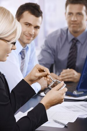 Businesswoman using PDA at office meeting, coworkers smiling in background. photo