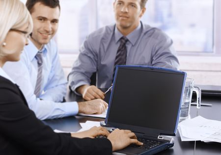 Professionals at meeting working together, businesswoman typing on laptop keyboard. Focus on laptop. photo