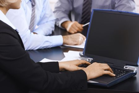 Hands in closeup, typing on laptop keyboard, colleagues in the background. Stock Photo - 6508248