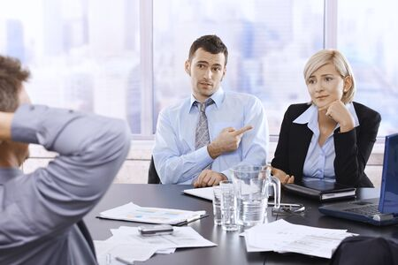 Troubled businesspeople in discussion at office meeting, businessman looking at boss blaming colleague. photo