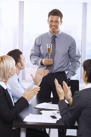 Businesspeople clapping hands, celebrating success of businessman holding glass of champagne. photo