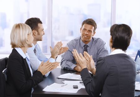 Businesspeople clapping hands, smiling and celebrating at meeting. photo