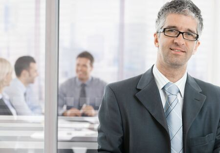 Gray haired businessman standing in front of meeting room, looking at camera, smiling. photo