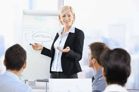 conducting: Business people sitting on presentation at office. Businesswoman presenting on whiteboard.