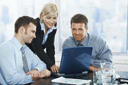 boardroom meeting: Smiling mid-adult businesspeople at meeting looking at laptop in office.