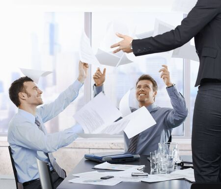 Laughing businessmen throwing documents up into the air sitting in office. photo