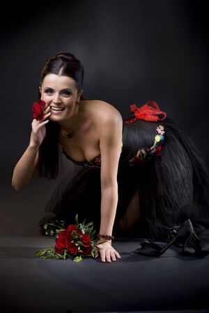 Beautiful young woman wearing a black cocktail dress knealing in sexy pose, holding a red rose between her teeth. photo