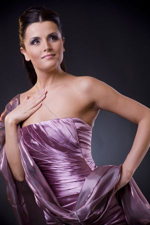 Beautiful young woman posing, wearing a light purple evening dress with stole. photo