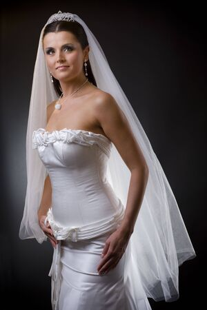 wedding photography: Studio portrait of a young bride wearing white wedding dress with veil, smiling and looking at camera.