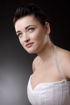 Portrait of a beautiful young bride wearing white wedding dress, smiling. photo